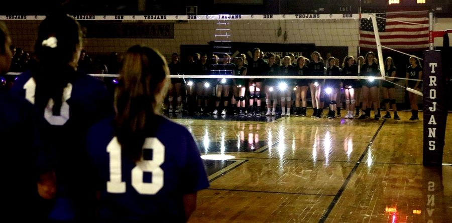 Downers Grove North and York players shine flashlights on their phones Tuesday night and display purple bracelets in memory of Beth Dunlap, a Downers North volleyball player struck and killed outside the school in February.