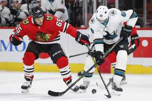 Chicago Blackhawks center Andrew Shaw, left, battles for the puck with San Jose Sharks center Melker Karlsson, right, during the first period of an NHL hockey game Thursday, Oct. 10, 2019, in Chicago.