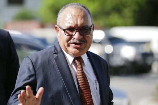 FILE - In this Nov. 14, 2018, file photo, Papua New Guinea Prime Minister Peter O'Neill gestures after inspecting the APEC 2018 International Media Center at Port Moresby, Papua New Guinea. Papua New Guinea police say they have an arrest warrant for former Prime Minister O'Neill for official corruption. The acting police commissioner said O'Neill was in a hotel in the capital but refusing to cooperate.