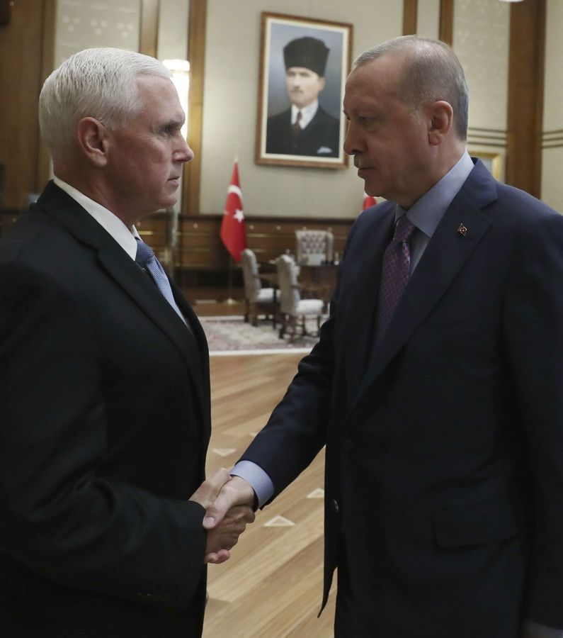 U. S. Vice President Mike Pence, left, and Turkish President Recep Tayyip Erdogan shake hands before their talks at the presidential palace, in Ankara, Turkey, Thursday, Oct. 17, 2019.  A high level U.S. delegation arrived in Turkey on Thursday for talks on a cease-fire in Syria. (Presidential Press Service via AP, Pool )