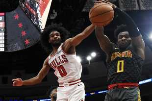 Bulls guard Coby White, left, and Atlanta Hawks guard Brandon Goodwin go for a loose ball during the first half of on Thursday night in Chicago. White went off for 29 points as the Bulls closed the preseason with a win.