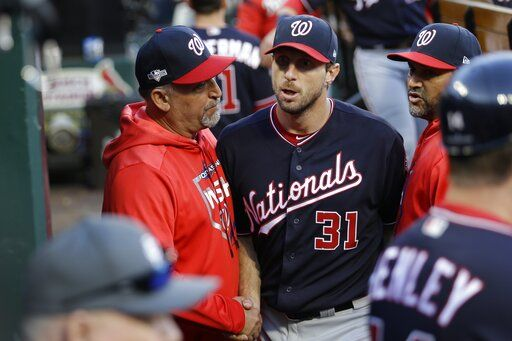 Washington Nationals manager Dave Martinez congratulates starting pitcher Max Scherzer after getting through the seventh inning of Game 2 of the baseball National League Championship Series against the St. Louis Cardinals Saturday, Oct. 12, 2019, in St. Louis.