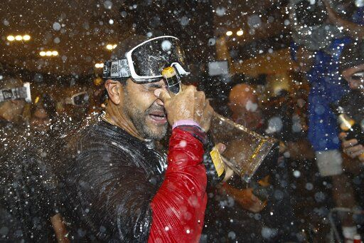 Washington Nationals manager Dave Martinez celebrates after Game 4 of the baseball National League Championship Series against the St. Louis Cardinals Wednesday, Oct. 16, 2019, in Washington. The Nationals won 7-4 to win the series 4-0.
