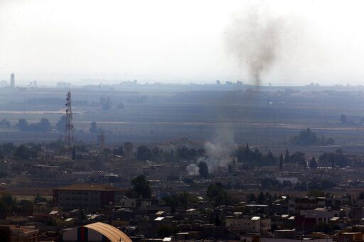 In this photo taken from the Turkish side of the border between Turkey and Syria, in Ceylanpinar, Sanliurfa province, southeastern Turkey, smoke billows from targets in Ras al-Ayn, Syria, caused by shelling by Turkish forces, Friday, Oct. 18, 2019. Fighting continued in a northeast Syrian border town at the center of the fight between Turkey and Kurdish forces early Friday, despite a U.S.-brokered cease-fire that went into effect overnight. Shelling and gunfire could be heard in and around Ras al-Ayn, as smoke billowed from locations near the border with Turkey and the Turkish town of Ceylanpinar.