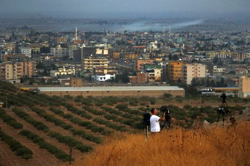 Members of the media work on a hilltop overlooking the border town of Ceylanpinar, Sanliurfa province, southeastern Turkey, and further in the background Ras al-Ayn, Syria, Friday, Oct. 18, 2019. Fighting broke out in the morning hours in the Syrian border town which has been a flashpoint in the fight between Turkey and Kurdish forces despite a U.S.-brokered cease-fire that went into effect overnight. The fighting died down in mid-morning.