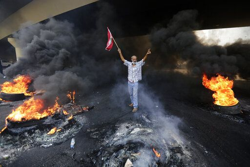 An anti-government protester makes victory sign, as he holds a Lebanese national flag and walks fire of tires that sits to block a road during a protest against government's plans to impose new taxes in Beirut, Lebanon, Friday, Oct. 18, 2019. Demonstrators in Lebanon are blocking major roads across the country in a second day of protests against proposed new taxes, which come amid a severe economic crisis.