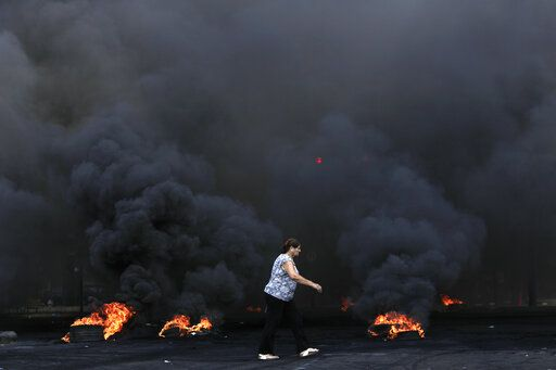 A woman walks by burning tires that were set fire to block a road during a protest against government's plans to impose new taxes in Beirut, Lebanon, Friday, Oct. 18, 2019. The protests erupted over the government's plan to impose new taxes during a severe economic crisis, with people taking their anger out on politicians they accuse of corruption and decades of mismanagement.