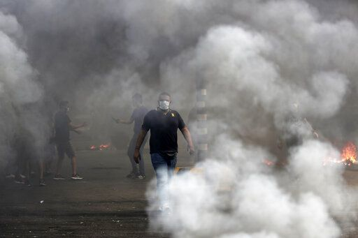 An anti-government protester walks between burning tires that were set fire to block a road during a protest against government's plans to impose new taxes in Beirut, Lebanon, Friday, Oct. 18, 2019. Demonstrators in Lebanon are blocking major roads across the country in a second day of protests against proposed new taxes, which come amid a severe economic crisis.