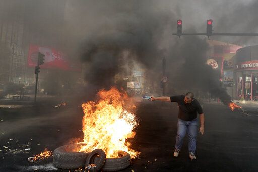 An anti-government protester sets fire on tires to block a road during a protest against government's plans to impose new taxes in Beirut, Lebanon, Friday, Oct. 18, 2019. The protests erupted over the government's plan to impose new taxes during a severe economic crisis, with people taking their anger out on politicians they accuse of corruption and decades of mismanagement.