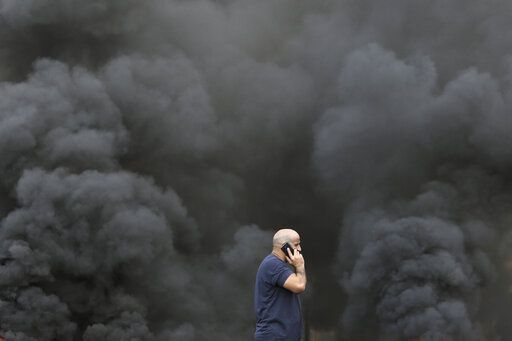 A man speaks on his smartphone while walking by black smoke from burning tires that were set on fire to block a road during a protest against government's plans to impose new taxes in Beirut, Lebanon, Friday, Oct. 18, 2019. The protests erupted over the government's plan to impose new taxes during a severe economic crisis, with people taking their anger out on politicians they accuse of corruption and decades of mismanagement.