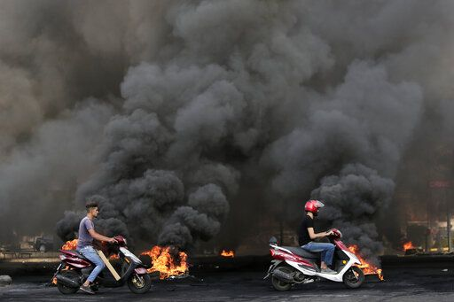 Men on scooters pass tires that were set on fire to block a road during a protest against government's plans to impose new taxes in Beirut, Lebanon, Friday, Oct. 18, 2019. The protests erupted over the government's plan to impose new taxes during a severe economic crisis, with people taking their anger out on politicians they accuse of corruption and decades of mismanagement.
