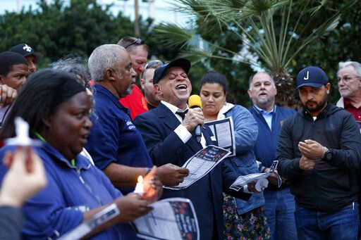 "New Orleans music legend Deacon John Moore sings ""Amazing Grace"" during a candlelight vigil outside city hall for deceased and injured workers from the Hard Rock Hotel construction collapse Sat., Oct. 12, in New Orleans, on Thursday, Oct. 17, 2019. The vigil was organized by various area labor groups."