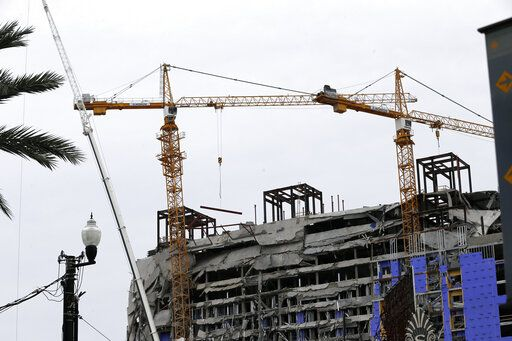 Two unstable cranes loom over the construction of a Hard Rock Hotel, Thursday, Oct. 17, 2019, in New Orleans.  The 18-story hotel project that was under construction collapsed last Saturday, killing three workers. Two bodies remain in the wreckage. Authorities say explosives will be strategically placed on the two unstable construction cranes in hopes of bringing them down with a series of small controlled blasts ahead of approaching tropical weather.