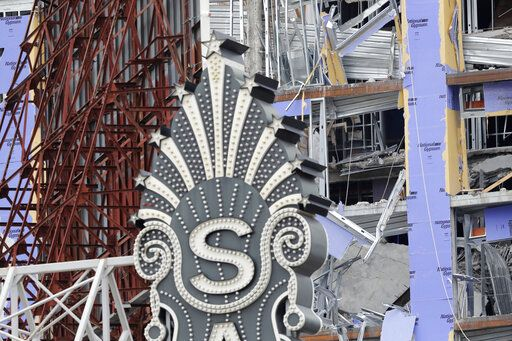 The Saenger Theater sign is seen in the foreground of the damaged Hard Rock Hotel, Thursday, Oct. 17, 2019, in New Orleans.  The 18-story hotel project that was under construction collapsed last Saturday, killing three workers. Two bodies remain in the wreckage.