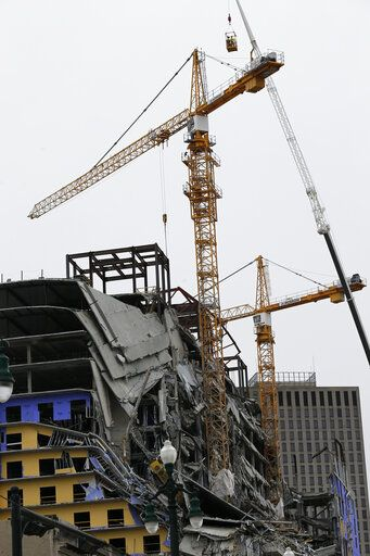 Workers in a bucket, top, begin the process of planting explosive charges on two unstable cranes at the Hard Rock Hotel, which underwent a partial, major collapse on Saturday, Oct. 12, in New Orleans, viewed on Thursday, Oct. 17, 2019. Authorities say explosives will be strategically placed on the two unstable construction cranes in hopes of bringing them down with a series of small controlled blasts ahead of approaching tropical weather. Officials hope to bring the towers down Friday without damaging nearby businesses and historic buildings in and around the nearby French Quarter.
