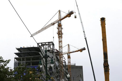 Workers in a bucket begin the process of planting explosive charges on two unstable cranes at the Hard Rock Hotel, which underwent a partial, major collapse Saturday, Oct. 12, in New Orleans, viewed Thursday, Oct. 17, 2019. Authorities say explosives will be strategically placed on the two unstable construction cranes in hopes of bringing them down with a series of small controlled blasts ahead of approaching tropical weather. Officials hope to bring the towers down Friday without damaging nearby businesses and historic buildings in and around the nearby French Quarter.