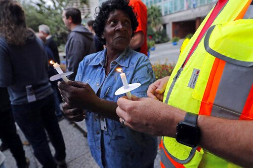 People hold candles during a candlelight vigil outside city hall for deceased and injured workers from the Hard Rock Hotel construction collapse Sat., Oct., 12, in New Orleans, on Thursday, Oct. 17, 2019. The vigil was organized by various area labor groups.