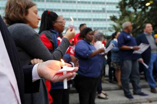 People hold candles during a candlelight vigil outside city hall for deceased and injured workers from the Hard Rock Hotel construction collapse Sat., Oct. 12, in New Orleans, on Thursday, Oct. 17, 2019. The vigil was organized by various area labor groups.