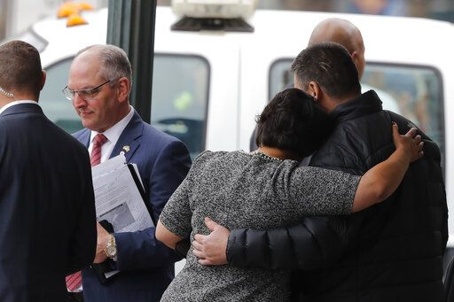 New Orleans Mayor Latoya Cantrell comforts the brother of one of the deceased workers as Louisiana Gov. John Bel Edwards walks away after giving his condolences, near the Hard Rock Hotel, Thursday, Oct. 17, 2019, in New Orleans.  The 18-story hotel project that was under construction collapsed last Saturday, killing three workers. Two bodies remain in the wreckage.