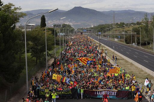 Protesters match into the city on the fifth day of protests over the conviction of a dozen Catalan independence leaders in Barcelona, Spain, Friday, Oct. 18, 2019. Various flights into and out of the region are cancelled Friday due to a general strike called by pro-independence unions and five marches of tens of thousands from inland towns are expected converge in Barcelona's center on Friday afternoon for a mass protest with students to and workers who are on strike.