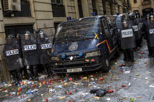 Spanish police stand outside a police station surrounded of objects thrown by pro-independence demonstrators in Barcelona, Spain, Friday, Oct. 18, 2019. Various flights into and out of the region are cancelled Friday due to a general strike called by pro-independence unions and five marches of tens of thousands from inland towns are expected converge in Barcelona's center on Friday afternoon for a mass protest with students to and workers who are on strike.