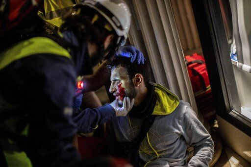 Paramedics attend a protestor during clashes with police in Barcelona, Spain, early Friday, Oct. 18, 2019. Catalonia's separatist leader vowed Thursday to hold a new vote to secede from Spain in less than two years as the embattled northeastern region grapples with a wave of violence that has tarnished a movement proud of its peaceful activism.