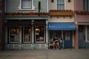 In this Oct. 11, 2019 photo, visitors sits outside a shop on the Main Street at Hong Kong Disneyland in Hong Kong. The body-blow of months of political protests on Hong Kong's tourism is verging on catastrophic for one of the world's great destinations. Geared up to receive 65 million travelers a year, the city's hotels, retailers, restaurants and other travel-oriented industries are suffering. But some intrepid visitors came specifically to see the protests and are reveling in deep discounts and unusually short lines at tourist hotspots. (AP Photo/Felipe Dana)
