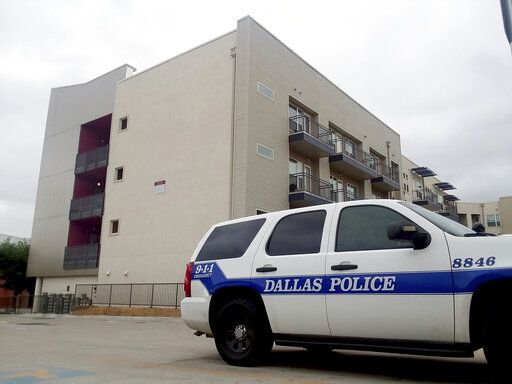 FILE - In this Sept. 10, 2018, file photo, a Dallas Police vehicle is parked near the South Side Flats apartments in Dallas. Former Dallas Police Officer Amber Guyger fatally shot an unarmed black neighbor whose apartment she said she entered by mistake, believing it to be her own. It's unclear when Guyger first talked to investigators about the September 2018 shooting, but she was eventually charged and is serving 10 years in prison after being convicted of murder this month.