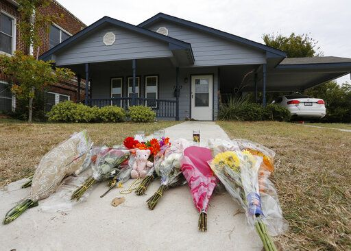 FILE - In this Monday, Oct. 14, 2019 photo, flowers lie on the sidewalk in front of the house in Fort Worth, Texas, where a white Fort Worth police officer Aaron Dean shot and killed Atatiana Jefferson, a black woman, through a back window of her home. Dean resigned before he could be compelled to undergo questioning. After a police officer fatally shoots someone, it can take days or even weeks before the public or his supervisors hear the officer's version of what happened.