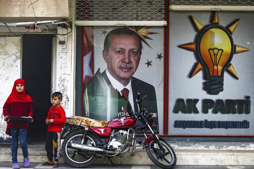 Turkish children stand in front of a billboard with a picture of Turkey's President Recep Tayip Erdogan and a poster of his ruling Justice and Development Party, AKP, in the border town of Akcakale, Sanliurfa province, southeastern Turkey, Friday, Oct. 18, 2019. The cease-fire in northern Syria got off to a rocky start Friday, as Kurdish leaders accused Turkey of violating the accord with continued fighting at a key border town while casting doubt on provisions in the U.S.-brokered deal with Ankara.