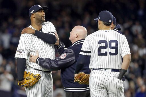 New York Yankees trainer Steve Donohue, center, checks on pitcher CC Sabathia during the eighth inning of Game 4 of baseball's American League Championship Series against the Houston Astros, Thursday, Oct. 17, 2019, in New York.