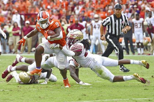 Clemson's Travis Etienne (9) runs out of the tackle attempt by Florida State's Akeem Dent during the first half of an NCAA college football game Saturday, Oct. 12, 2019, in Clemson, S.C.