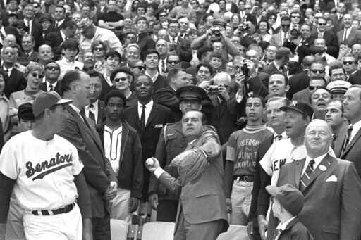 FILE - In this April 7, 1969, file photo, President Richard M. Nixon throws out the ceremonial first pitch in Washington as Baseball Commissioner Bowie Kuhn, second from left, and Washington Senators manager Ted Williams, far left, and others, look on. Growing up in the Washington suburbs during the 1960s, the local baseball team was a lost cause, except for a winning record for the expansion Senators after Ted Williams was lured out of retirement to manage the team.