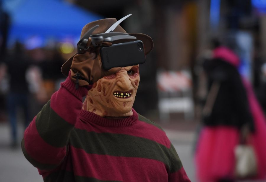 Freddy Krueger carefully films the atmosphere at the annual Nightmare on Chicago Street festival in Elgin Saturday.