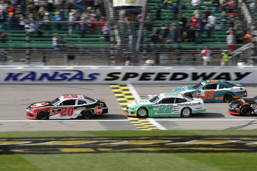 Christopher Bell (20) leads Austin Cindric (22) and Brandon Jones (19) during the first lap of an NASCAR Xfinity Series auto race at Kansas Speedway in Kansas City, Kan., Saturday, Oct. 19, 2019.