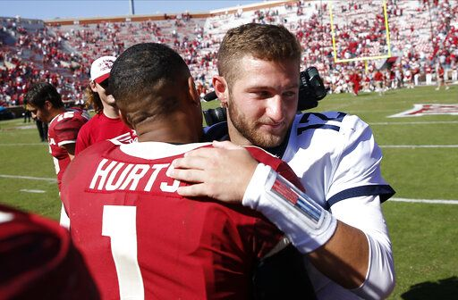 West Virginia quarterback Austin Kendall (12) and Oklahoma quarterback Jalen Hurts (1) embrace following an NCAA college football game in Norman, Okla., Saturday, Oct. 19, 2019. Oklahoma won 52-14.