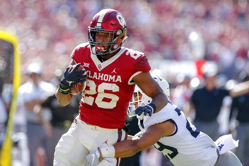 Oklahoma running back Kennedy Brooks (26) runs for a first down against West Virginia during the first half of an NCAA college football game in Norman, Okla., Saturday, Oct. 19, 2019.