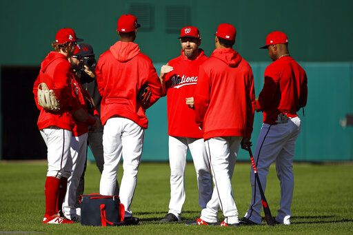 Washington Nationals third base coach Bob Henley, center, speaks with players during a baseball workout, Friday, Oct. 18, 2019, in Washington, in advance of the team's appearance in the World Series.