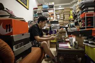 Tian Hao, a sneaker collector and trader, browse through one of the trading apps while sitting among boxes of shoes crammed into the living room of his apartment in Beijing on Sept. 25, 2019.