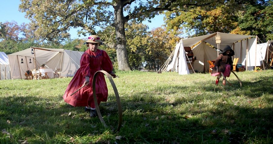 Alice Urven, 7, of Fond du Lac, Wisconsin, plays with a hoop and stick Sunday during the Civil War Encampment and Battle at the Northbrook Sports Club in Hainesville.