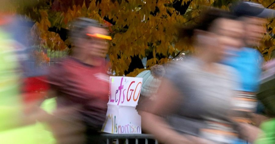 Alli Wiertel, 10, of Oswego holds a sign encouraging runners Sunday as they pass by during the seventh annual Healthy Driven Naperville Half Marathon.