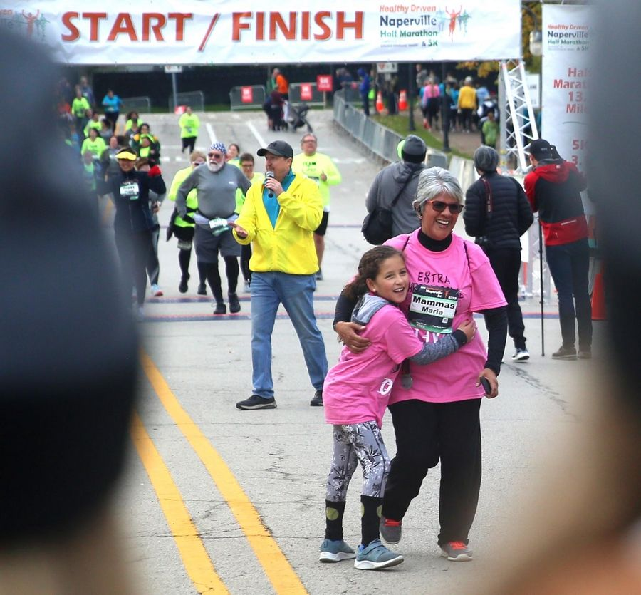 Maria Martinez of Plainfield and her granddaughter Julissa Rosario, 8, of Naperville enjoy the moment Sunday as they finish the seventh annual Healthy Driven Naperville 5K.