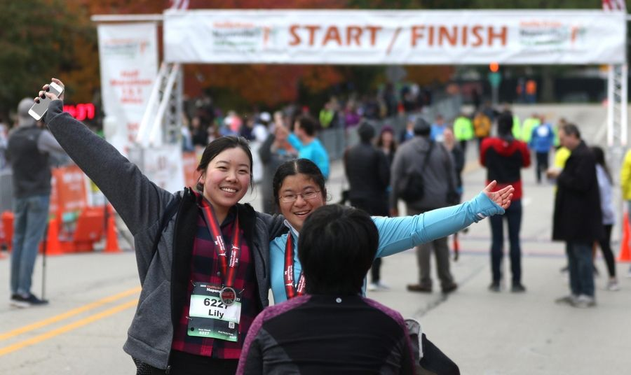 Lily Feng, left, and Shirley Xiao, right, celebrate after completing the seventh annual Healthy Driven Naperville 5K Sunday morning. Both are from Naperville.