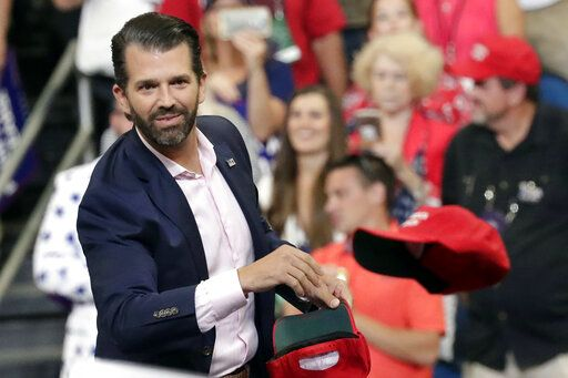 FILE - In this June 18, 2019, file photo, Donald Trump Jr. throws hats to supporters at a campaign rally for President Donald Trump in Orlando, Fla.