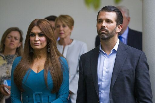 FILE- - In this July 11, 2019, file photo, Donald Trump Jr., the son of President Donald Trump, right, and his girlfriend Kimberly Guilfoyle, listen as President Donald Trump speaks about the 2020 census in the Rose Garden of the White House in Washington.