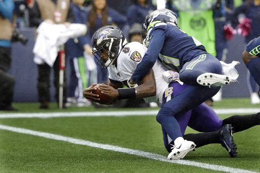 Baltimore Ravens quarterback Lamar Jackson (8) is hit by Seattle Seahawks cornerback Tre Flowers while scoring a touchdown on a fourth-down keeper play during the second half of an NFL football game, Sunday, Oct. 20, 2019, in Seattle.