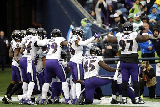 Baltimore Ravens players take part in a group photo touchdown celebration after cornerback Marlon Humphrey recovered a fumble and ran for a touchdown during the second half of an NFL football game against the Seattle Seahawks, Sunday, Oct. 20, 2019, in Seattle.