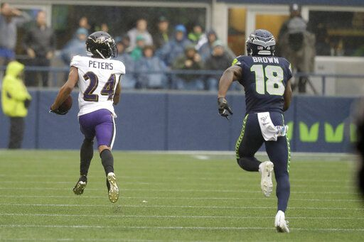 Baltimore Ravens cornerback Marcus Peters (24) runs for a touchdown after he intercepted a pass intended for Seattle Seahawks wide receiver Jaron Brown (18) during the first half of an NFL football game, Sunday, Oct. 20, 2019, in Seattle.