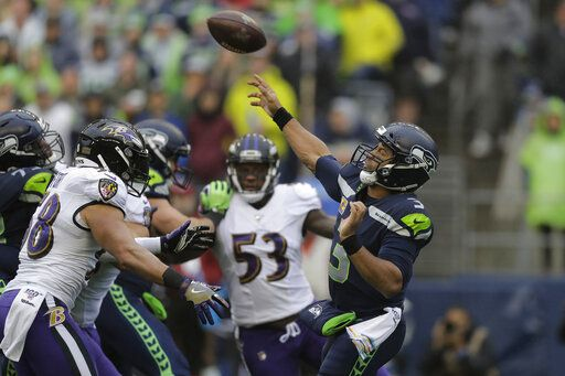 Seattle Seahawks quarterback Russell Wilson (3) passes under pressure from Baltimore Ravens linebacker L.J. Fort, left, during the first half of an NFL football game, Sunday, Oct. 20, 2019, in Seattle.