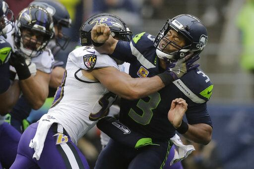 Seattle Seahawks quarterback Russell Wilson (3) is hit after he passed under pressure from Baltimore Ravens linebacker L.J. Fort, left, during the first half of an NFL football game, Sunday, Oct. 20, 2019, in Seattle.